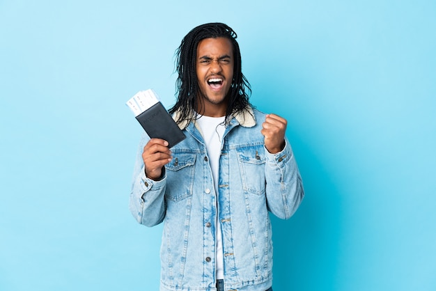 Young african american man with braids isolated on blue background happy in vacation with passport and plane tickets