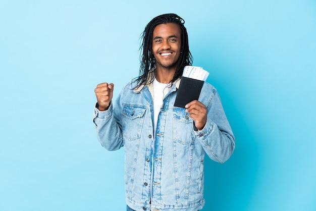 パスポートと親指を上にして飛行機を保持している休暇中に青い壁に分離された三つ編みを持つ若いアフリカ系アメリカ人