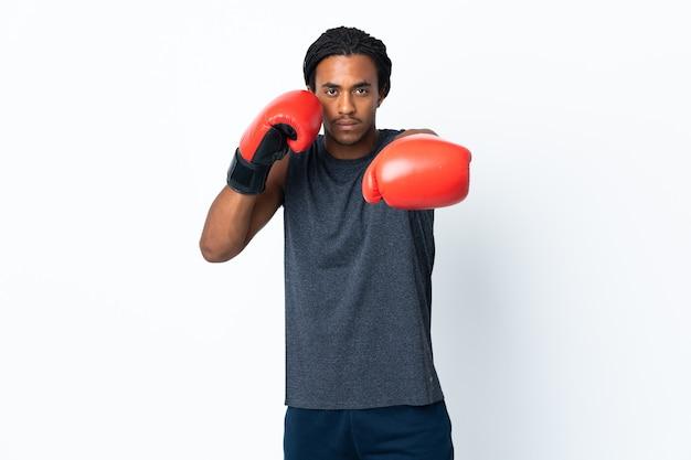 Молодой афроамериканец с косами, изолированные на фиолетовом фоне с боксерскими перчатками