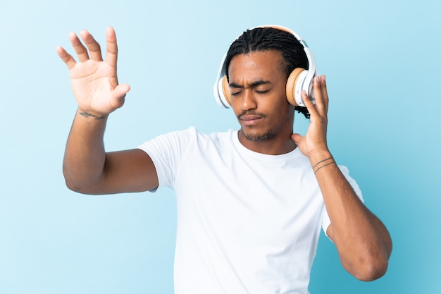 Молодой афроамериканец с косами на синем слушает музыку и танцует