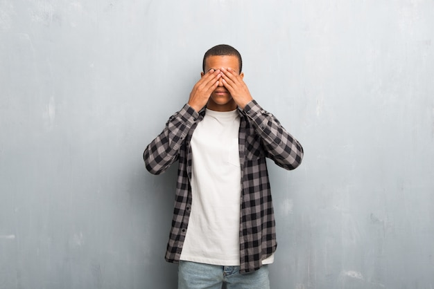 Young african american man with checkered shirt covering eyes by hands