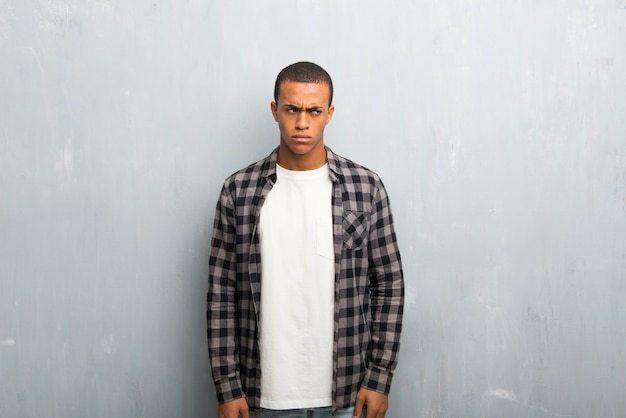 Young african american man with checkered shirt feeling upset