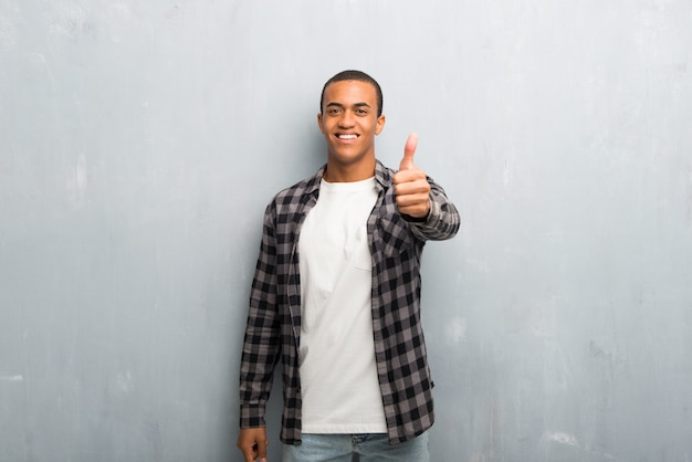 Young african american man with checkered shirt giving a thumbs up gesture