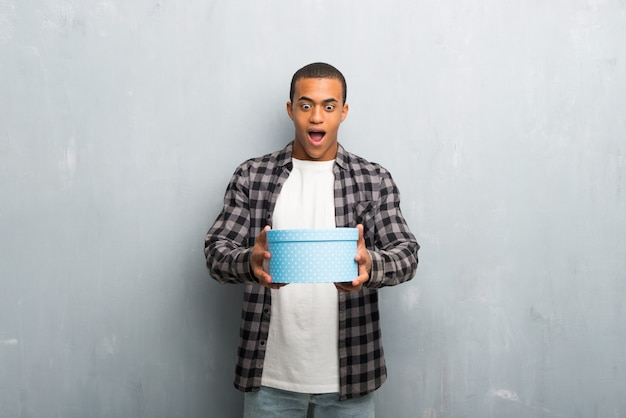 Young african american man with checkered shirt holding gift boxes in hands
