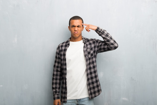 Young african american man with checkered shirt making the gesture of madness putting finger