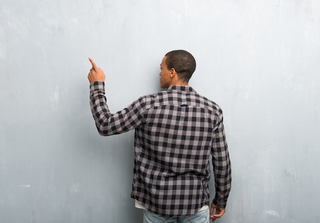 Young african american man with checkered shirt pointing back with the index finger