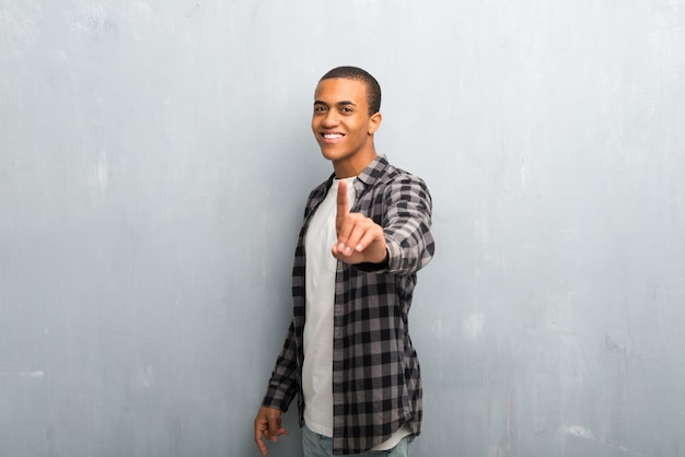 Young african american man with checkered shirt showing and lifting a finger