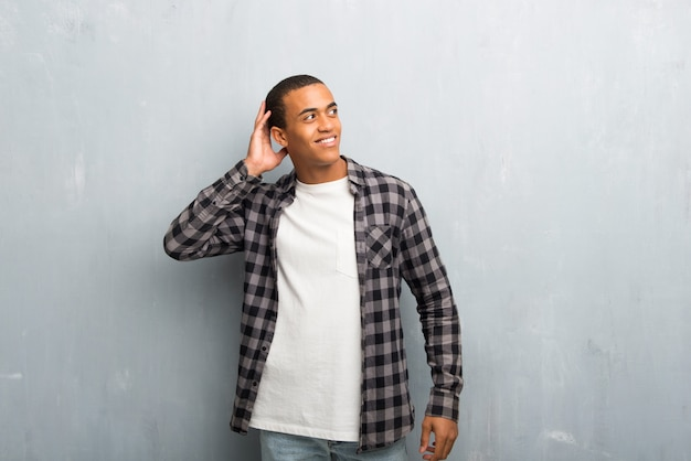Young african american man with checkered shirt thinking an idea while scratching head