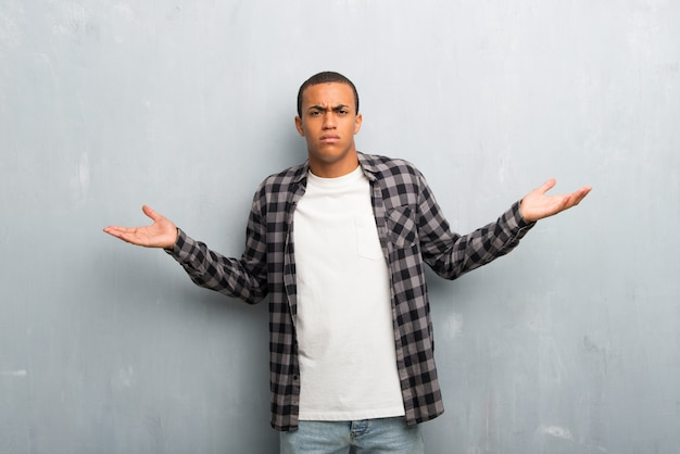 Young african american man with checkered shirt unhappy and frustrated