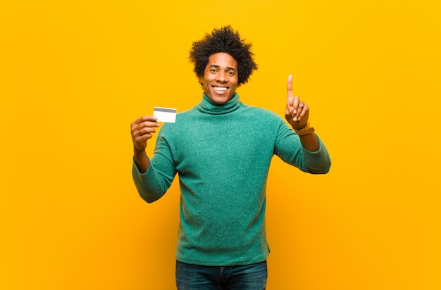 Young african american man with a credit card on orange