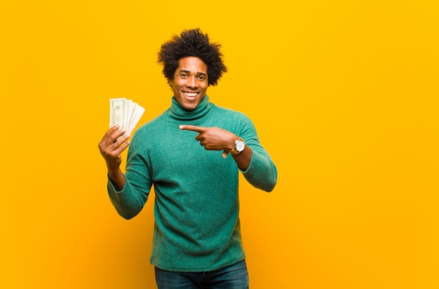 Young african american man with dollar bills against orange back