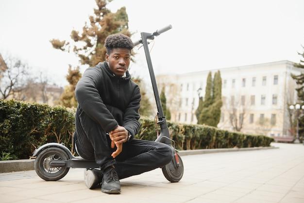 Молодой афро-американский мужчина с электросамокатом в городе