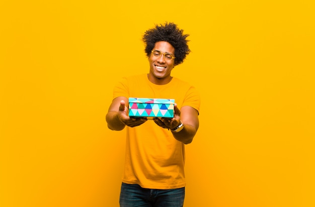 Young african american man with a gift box against orange