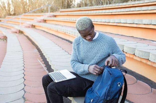 座っているラップトップコンピューターを持つ若いアフリカ系アメリカ人の男