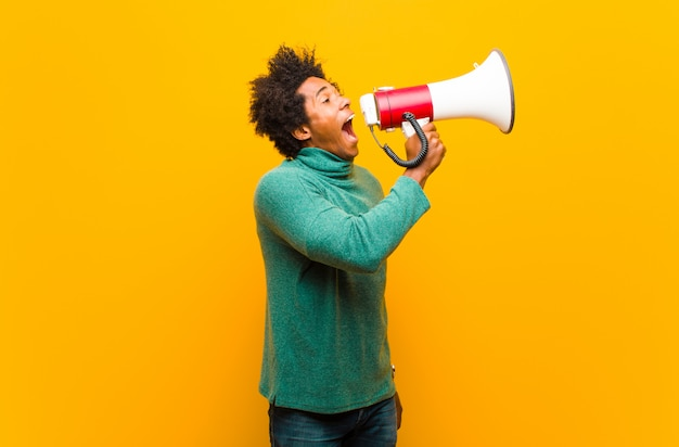 Young african american man with a megaphone on orange