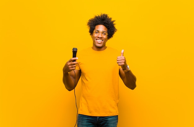 Young african american man with a microphone singing  against or