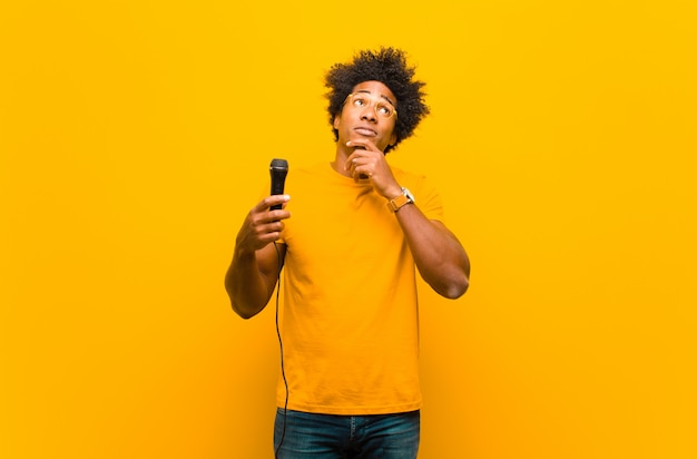 Young african american man with a microphone singing   or