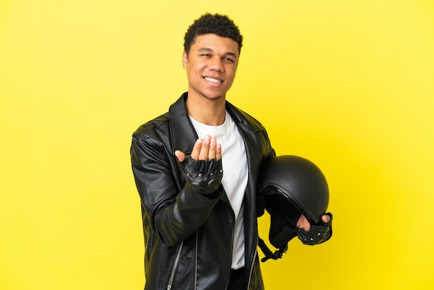 Young african american man with a motorcycle helmet isolated on yellow background inviting to come with hand. happy that you came