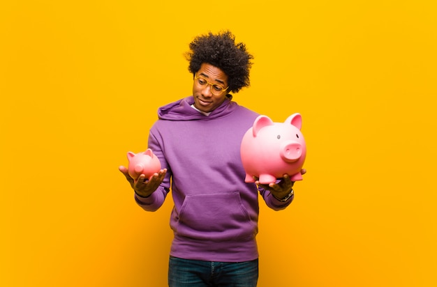 Young african american man with a piggy bank against orange back