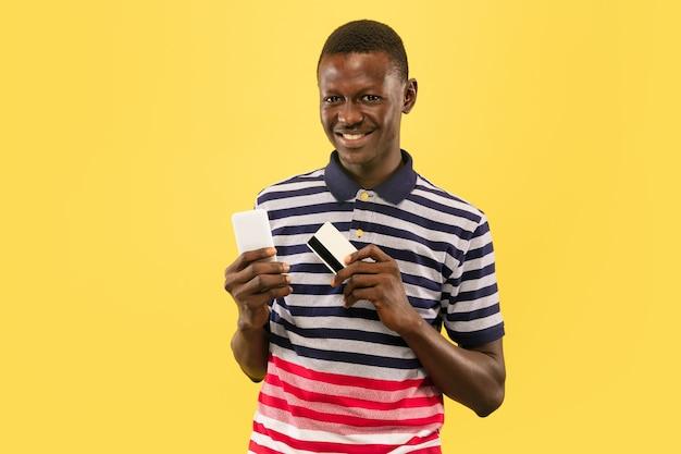 노란색 스튜디오 배경에 고립 된 스마트 폰 및 debet 카드와 젊은 아프리카 계 미국인 남자