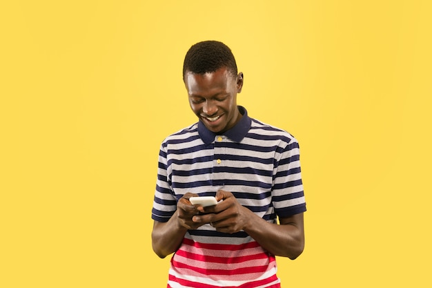 黄色のスタジオの背景、顔の表情に分離されたスマートフォンを持つ若いアフリカ系アメリカ人の男。美しい男性の半分の長さの肖像画。人間の感情、顔の表情の概念。