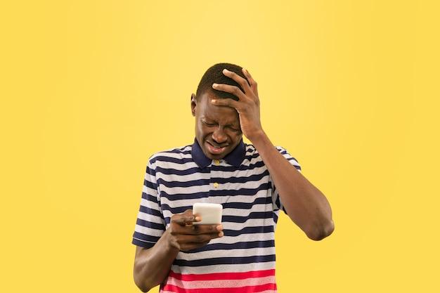 노란색 스튜디오 배경, 표정에 고립 된 스마트 폰으로 젊은 아프리카 계 미국인 남자. 아름다운 남성 절반 길이 초상화. 인간의 감정, 표정의 개념.