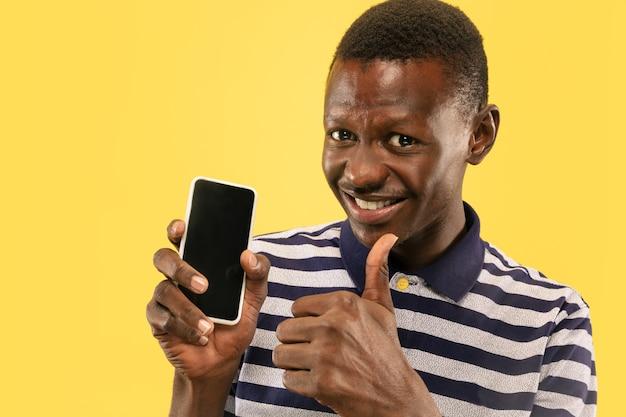 노란색 스튜디오 배경에 고립 된 스마트 폰으로 젊은 아프리카 계 미국인 남자