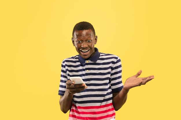 Young african-american man with smartphone isolated on yellow studio, facial expression.