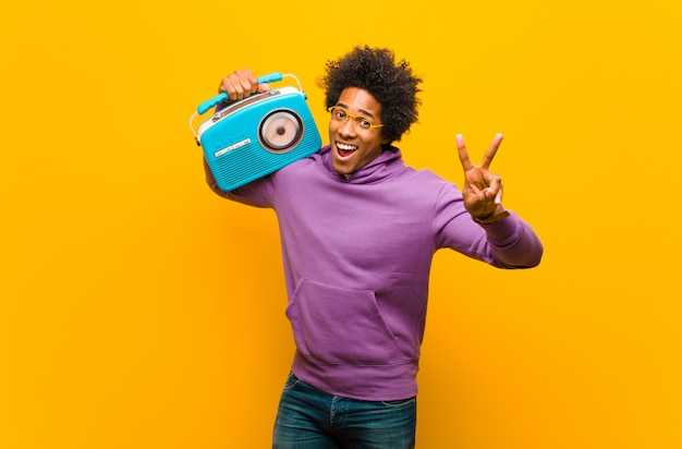 Young african american man with a vintage radio against orange b