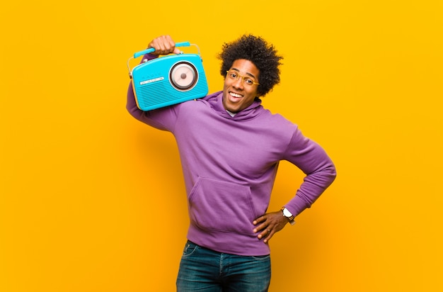 Young african american man with a vintage radio on orange