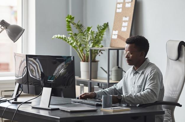 Молодой афро-американский мужчина, работающий за столом