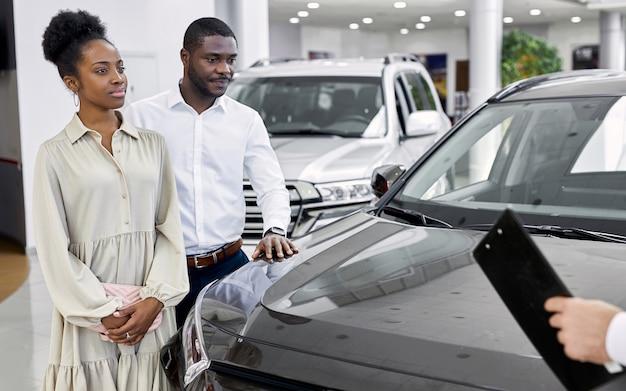若いアフリカ系アメリカ人の夫婦は将来の購入のために車を見に来ました