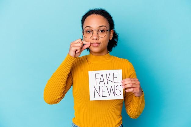 秘密を保持している唇に指で偽のニュースの概念を保持している若いアフリカ系アメリカ人の混血の女性。