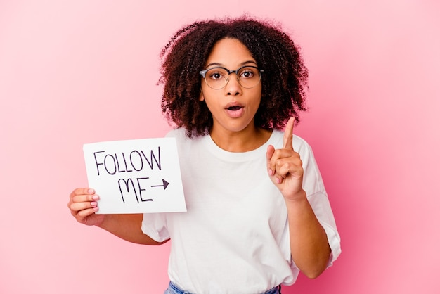 Молодая афро-американская женщина смешанной расы, держащая концепцию «следовать за мной», имеющая идею, концепцию вдохновения.