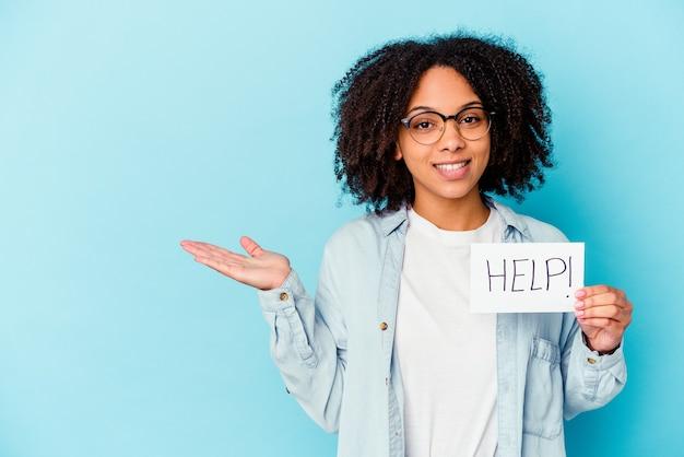 손바닥에 복사 공간을 표시 하 고 허리에 다른 손을 잡고 도움말 종이 개념을 들고 젊은 아프리카 계 미국인 혼혈 여자.