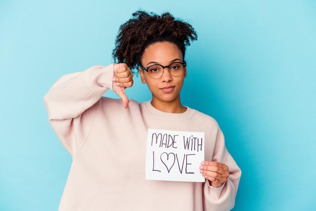 Молодая афро-американская женщина смешанной расы, держащая концепцию «сделано с любовью», показывая жест неприязни, пальцы вниз. концепция несогласия.