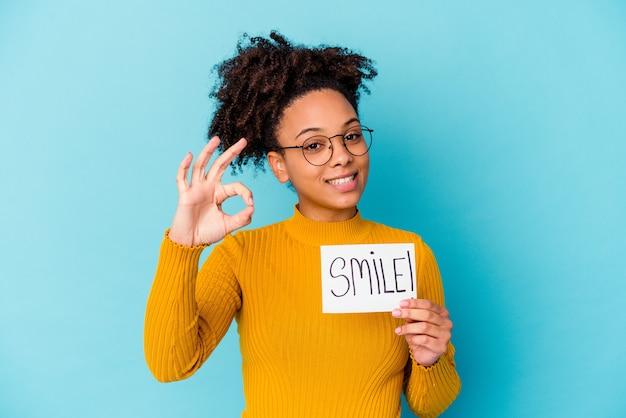 명랑 하 고 확인 제스처를 보여주는 자신감 미소 개념을 들고 젊은 아프리카 계 미국인 혼혈 여자.