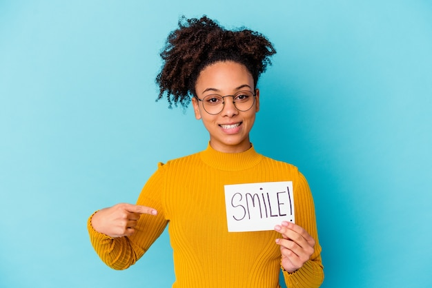 자랑스럽고 자신감이 셔츠 복사 공간을 손으로 가리키는 미소 개념 사람을 들고 젊은 아프리카 계 미국인 혼혈 여자