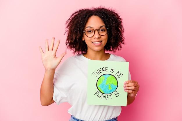 Молодая афро-американская женщина смешанной расы, держащая картон концепции защиты мира, улыбаясь, веселый показ номер пять с пальцами.