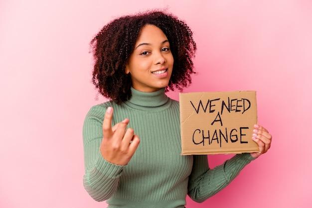 誘うようにあなたに指で指している感動的なメッセージ段ボールを持っている若いアフリカ系アメリカ人の混血の女性が近づいています。