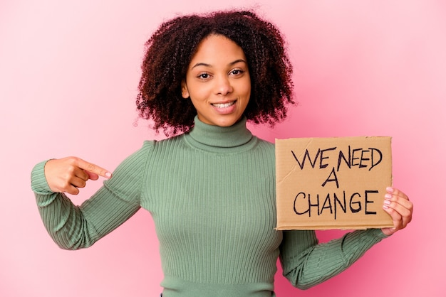 Young african american mixed race woman holding an inspiring message cardboard person pointing by hand to a shirt copy space, proud and confident