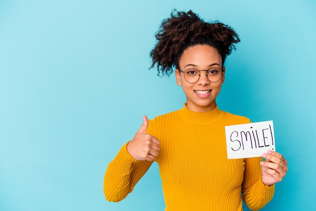 Young african american mixed race woman holding a smile concept smiling and raising thumb up