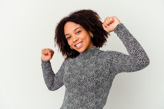 특별한 날을 축하하는 젊은 아프리카 계 미국인 혼혈 여자는 점프하고 에너지로 팔을 올립니다.