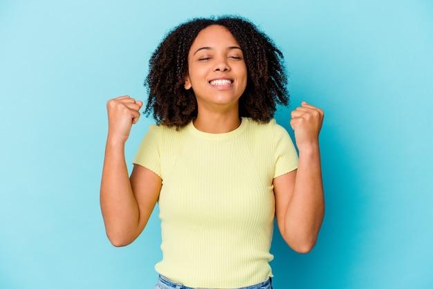 若いアフリカ系アメリカ人の混血の女性は、勝利、情熱と熱意、幸せな表現を祝って孤立しました。 Premium写真