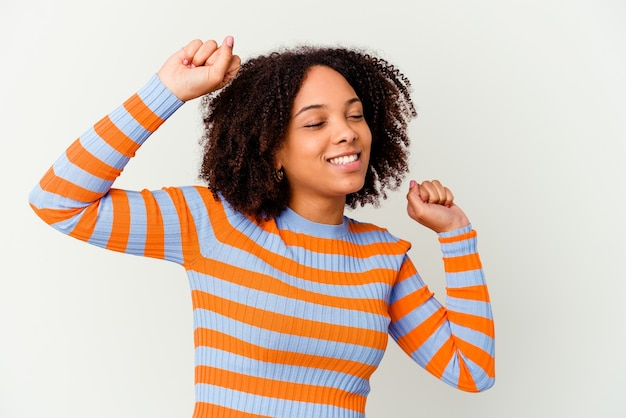 Young african american mixed race woman isolated celebrating a special day, jumps and raise arms with energy.