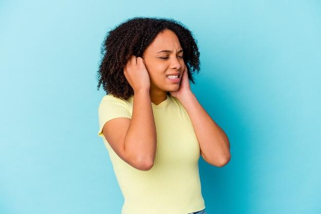 若いアフリカ系アメリカ人の混血の女性は、手で耳を覆って孤立しました。