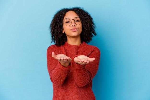 Молодая афро-американская женщина смешанной расы изолировала складывая губы и держась за ладони, чтобы послать воздушный поцелуй.