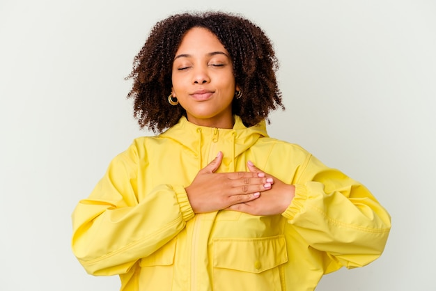 Young african american mixed race woman isolated has friendly expression, pressing palm to chest. love concept. Premium Photo