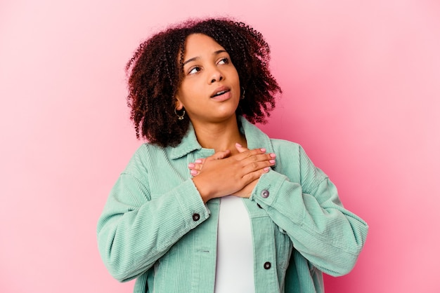 Young african american mixed race woman isolated has friendly expression, pressing palm to chest. love concept.