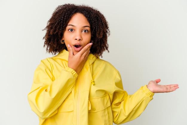 孤立した若いアフリカ系アメリカ人の混血の女性は、手のひらにコピースペースを保持し、頬を渡してください。驚きと喜び。